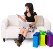 Una mujer sentada en un sofa, usa su ordenador y a su lado, sobre el suelo, unas bolsas de regalos