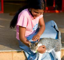 Chica joven acaricia a su gato sentada en el porche de su casa