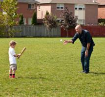 Padre e hijo juegan al beisball en el jardín de su casa