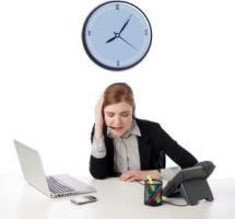 Una mujer trabaja sobre su escritorio y sobre ella cuelga un reloj sobre fondo blanco