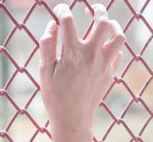 Primer plano de una mano apoyada en una verja de color rojo