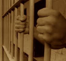 Primer plano de unas manos sobresaliendo entre las rejas de una celda dentro de una prisión