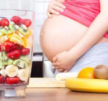 Mujer embarazada con batidora de frutas