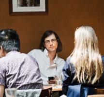 Reunión de amigos que charlan amistosamente en torno a una mesa