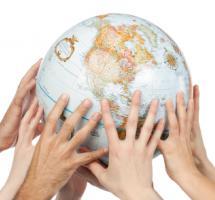 Varias manos sostienen un globo terraqueo