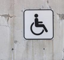 Señal pegada a la pared que indica paso para discapacitados