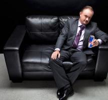 Plano general de un hombre de negocios sentado en un sillon y bebiendo una bebida energética