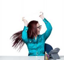 Mujer se divierte sentada en su mesa de trabajo