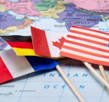 Diferentes banderas apoyadas sobre un mapa mundi