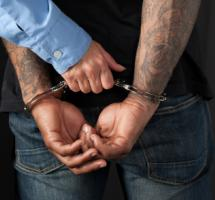 Persona esposada por la policía con las manos a la espalda