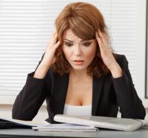 Mujer agobiada frente a su mesa de trabajo