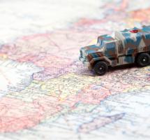 Camino de juguete militar sobre mapa mundi