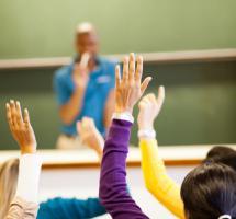 Clase con los almnos levantando las manos