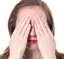 Mujer tapandose los ojos con amabas manos