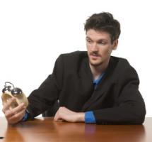 Persona en su puesto de trabajo sosteniendo un reloj entre las manos