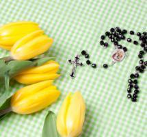 Flores y rosario sobre una mesa mantel
