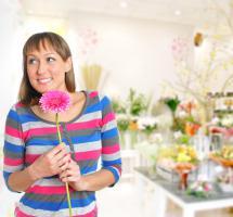 Mujer sonriente con flor entre las manos