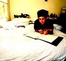 Un chico joven estudia sobre su cama dentro de su ahitación