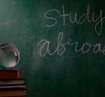 """Pizarra escolar con un mensaje escrito en tiza y en ingles que dice"""" Estudiar fuera"""""""