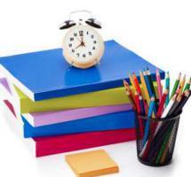 Bodegón de material escolar con un reloj encima de los libros