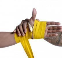 Primer plano de una mano aplicando un vendaje de color amarillo sobre fondo blanco