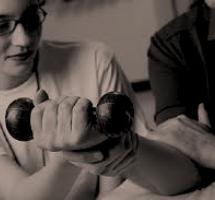 Fotografía en blanco y negro de una persona realizando ejercicio físico con una pesa en la mano supervisada por una especialista con gafas