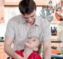 Padre e hija se miran complices en la cocina de su casa