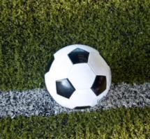 Plano cerrado de un balón de football sobre la cal del campo