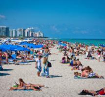 General de una playa repleta de gente, muchos tumbados tomando el sol