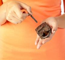 Plano cerrado de una mujer que cierra con una llave un candado que sostiene entre sus manos