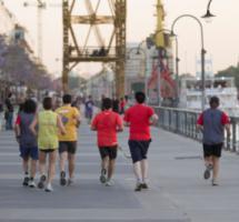 Un grupo de personas jóvenes corre por un paseo de un centro urbano