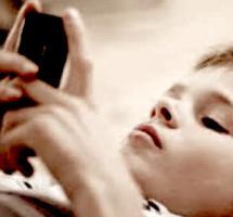 Plano muy cerrado de un niño jugando con un móvil tumbado en el suel