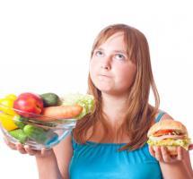 chica eligiendo entre comida hipercalórica y verduras